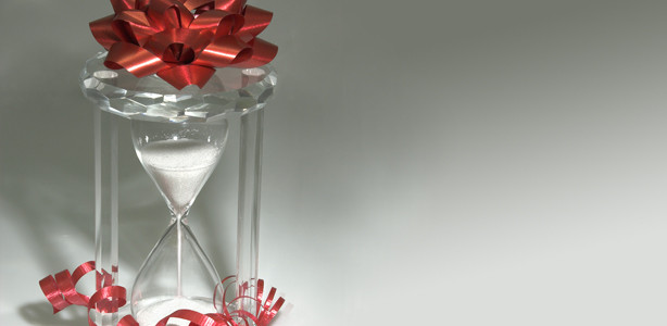 Clear hourglass filled with water with a gift bow on top