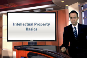 Man in business attire on a tv news desk in front of a screen displaying information on intellectual property.