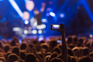 Concert crowd with arm rising holding smartphone to record stage