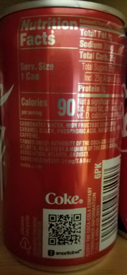 Coke specimen shows trademark use for soft drinks. The specimen is a photograph of a can of Coke. The trademark is shown above a QR code.