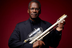 Inventor Lonnie Johnson holding prototype of the Supersoaker water gun made from PVC pipe
