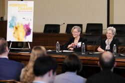 "Cherry Murray and Irina Buhimschi sit together on a panel and smile out at the audience. A poster for the event, proclaiming ""powering change"" is seen in the background."