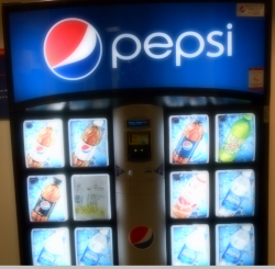 Pepsi specimen shows trademark use for soft drinks. The specimen is a photograph of a vending machine. The trademark is shown prominently at the top of the vending machine.