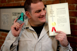 Inventor Steve Katsaros proudly holds up his Nokero solar lightbulb in one hand and the patent for the device in the other
