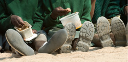 Children eating food in a barren climate with their shoes showing