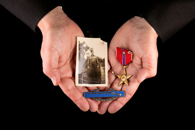 hands holding A Bronze Star, Combat Infantryman Badge, and 1945 portrait from Germany of Dean's grandfather, Herman Robichaux Sr., who served under General George S. Patton during the Battle of the Bulge.