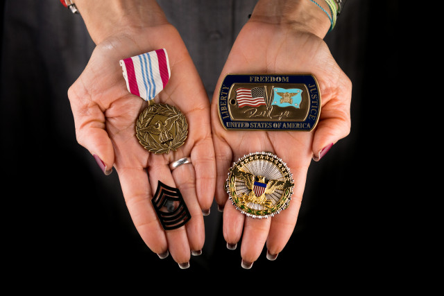 hands holding a Defense Meritorious Service Medal, a Challenge Coin from Secretary of Defense Donald Rumsfeld, an Office of the Secretary of Defense Identification Badge, and Master Gunnery Sergeant rank insignia.