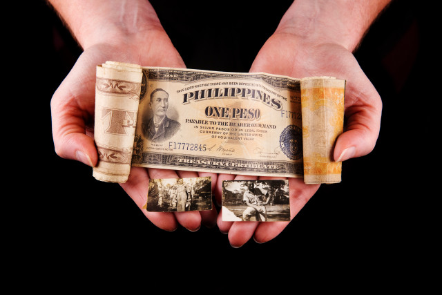 hands holding money roll, a collection of Allied Military Currency (AMC) from when holder's grandfather was stationed in the Philippines with the Army Air Corps, and photographs of grandfather during this time.