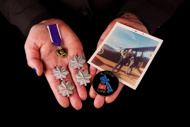 hands holding Purple Heart, a November 1965 photo of soldier loading radios into an O1E aircraft in Laos during the Vietnam War, a Ravens coin presented to soldier at a Ravens annual reunion, and out lieutenant colonel rank insignia
