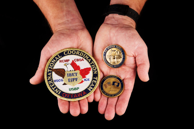 hands holding Challenge coins from the Secretary of Commerce and Chief, U.S. Border Patrol, and a patch from the United States, Canada Integrated Border Enforcement Team (IBET).