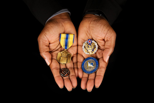 hands holding Air Force Commendation Medal, U.S. insignia, Challenge Coin from General John Jumper (Air Force Chief of Staff), and Headquarters Air Force Badge.