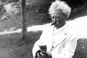 Black and White photo of author and humorist Samuel L. Clemens (Mark Twain) in white suit with kitten in Tuxedo Park, N.Y., circa 1907.