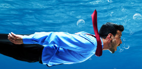 Man in shirt and tie swimming underwater