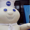 Photo of costume character Pillsbury Doughboy standing in front of the Expo booths.